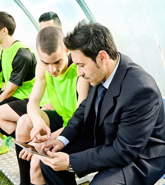 Football coach sitting at the sideline with the team looking at a digital tablet.